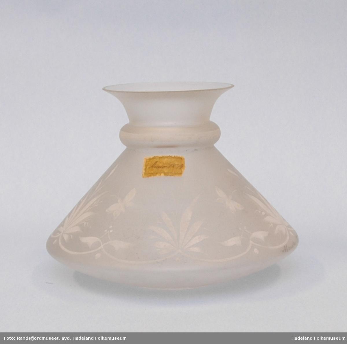 Frostet glass, hvit. rund, trekantet form som skrår inn mot toppen, for så å vende ut igjen og åpne seg. En vulst der hvor retningen skifter. Blomstermønster.