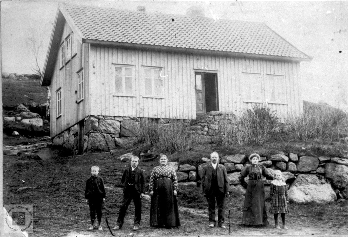 Familiegruppe foran huset ukjent sted trolig i Marnardal.