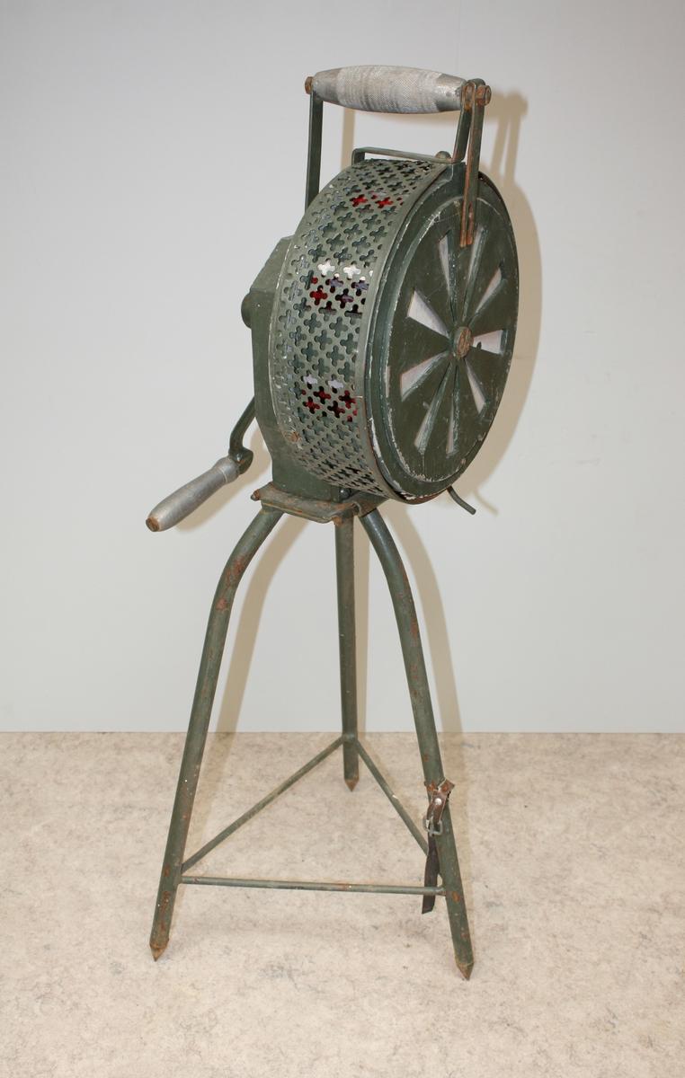 Manuell sirene som drives av en håndsveiv. Laget i jern/metall. Utstyrt med produksjonsskilt som viser produsent og produktnummer.