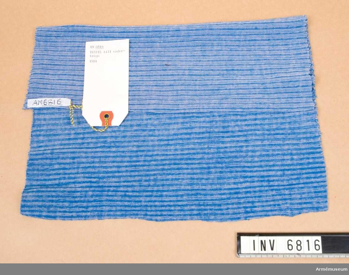 """Samhörande föremål är 6816 - 6817. Väv till undertröja för flygförare, prov, FMV. 1981.Mått 360 x 300 mm. Tunt elastiskt textilmaterial avsett för undertröja. Plaggens konstruktion är sådan att svetten har möjlighet att avdunsta direkt från huden. Detta betyder att huvuddelen av svetten  passerar genom plagget i ångform. Luftcirkulationen blir genom plaggens passform och elasticitet mycket låg vid huden. Textilmaterialet absorberar ej fukt och innehåller två ej  självbrinnande men smältbara fibrer. Det är en fabrikshemlighet  vad detta material egentligen innehåller och detta kunde vi  inte få veta. I samband med utställningen """"Rustning utrustning"""" 1981 fick vi detta material vilket också visades på utställningen."""