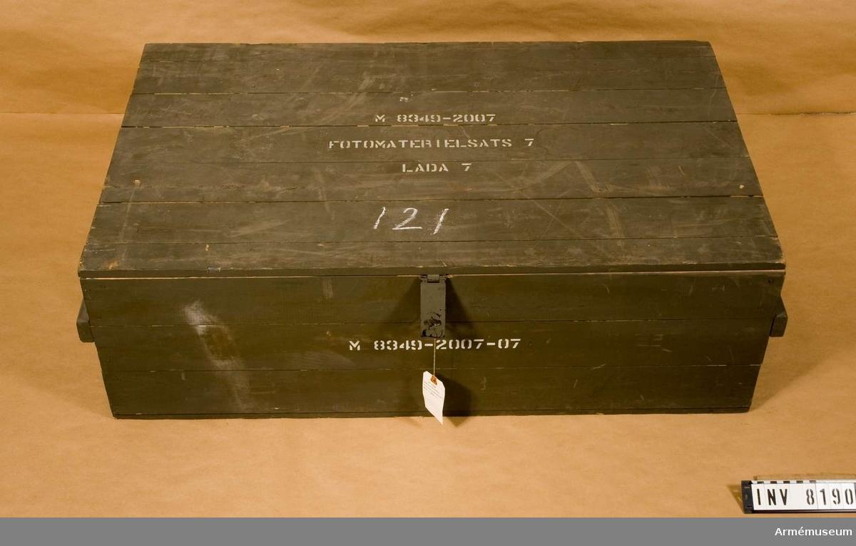 Samhörande nr är AM 8151 - 8199. Färgen är militärgrön.Text fram, på lock och kortsidor: M 8349-2007-07  (Fotomtrl. sats 7. Låda 7). Lådan är tom.Ur fotomaterielsats 7.
