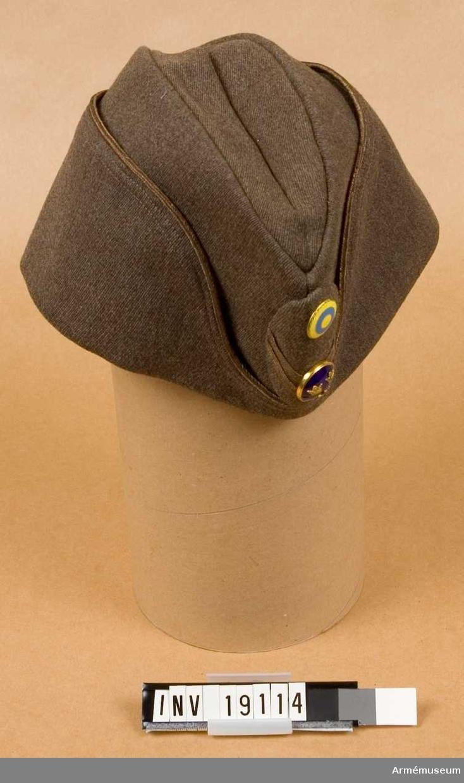 Av gråbrungrön kamgarnsdiagonal i reglementsenlig modell för löjtnant. Bronsfärgad galon runt brättet och ett elipsformat mjukt märke med officersknappen och nationalitetsmärket m/1941  och två smala vinklar =gradbeteckning för löjtnant.