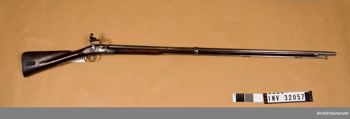 """Grupp E II.  Äldre modell för infanteriet. Loppets rel. l:64 kaliber.  1690-talet, senare försedd med järnladdstock.   Överlämnad enligt KAAD skrivelse 11/2 1880. dnr 469.Enligt uppgift i ett av Spaks kladdmanuskript till katalog över Artillerimuseum, vilket troligen är från cirka 1880, skulle """"å ett gammalt, förut vid varbygeln fästat papper ha stått: """"Mouquette de 1692 avec baionette, voye N:o, app, au Musée d'artillerie"""".Men i 1888 års tryckta katalog uppges, att en lapp med samma påskrift varit fäst vid varbygeln på det svenska geväret AM 4076 som då hade numret I:81. J. Alm."""