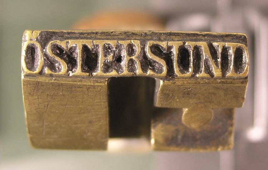 """Datumstämpel, med namnet """"ÖSTERSUND"""" i en linje. Detta ärtroligen en stympad fyrkantstämpel. Dessa användes en tid eftercirkelstämpelns intåg. Östersunds fyrkantstämpel tillverkades 1843och kan följas fram till 1858, då ram och årtalssiffror avlägsnades.Därefter användes den något år som ankomststämpel."""