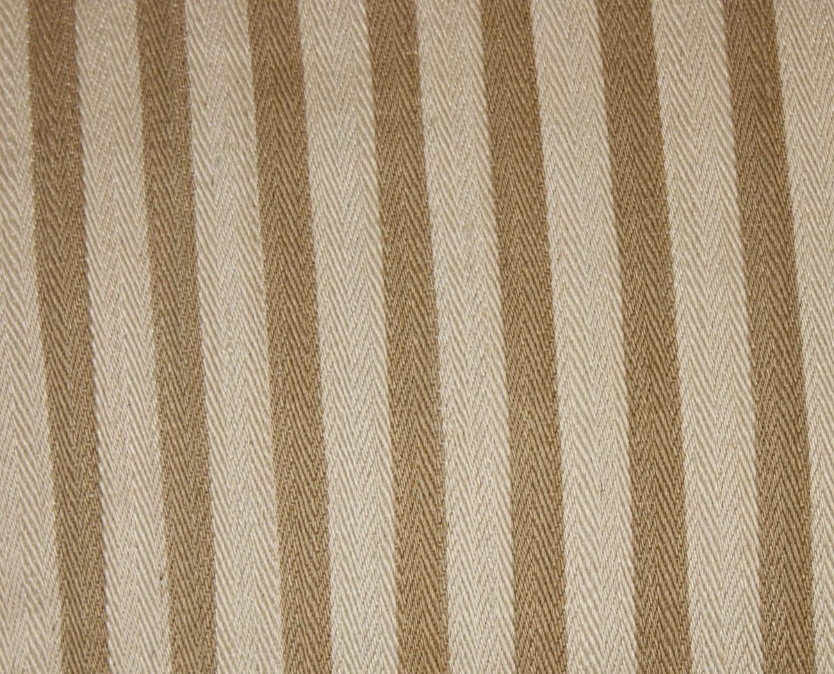 Kudde tillverkad av handvävt linnetyg, vävt i spetskypert, med varp randig i brunt och vitt och ljust enfärgat inslag. Ränderna ej kooordinerade med solvningen.  Fyllning av fjäder.
