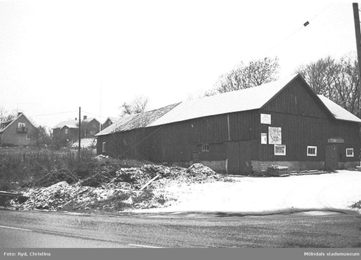 """Rondellbygge vid Ranntorp 1:3 i Lindome. Den nya """"trafikmaskinen"""" vid korsningen Gamla Riksvägen-Spårhagavägen slukade våren 1991 dessa förrådsbyggnader. De låg alldeles intill byn """"Nedre Rantorp"""", som då blev undersökt genom en arkeologisk utgrävning. Bilden är tagen under 1990-talet."""