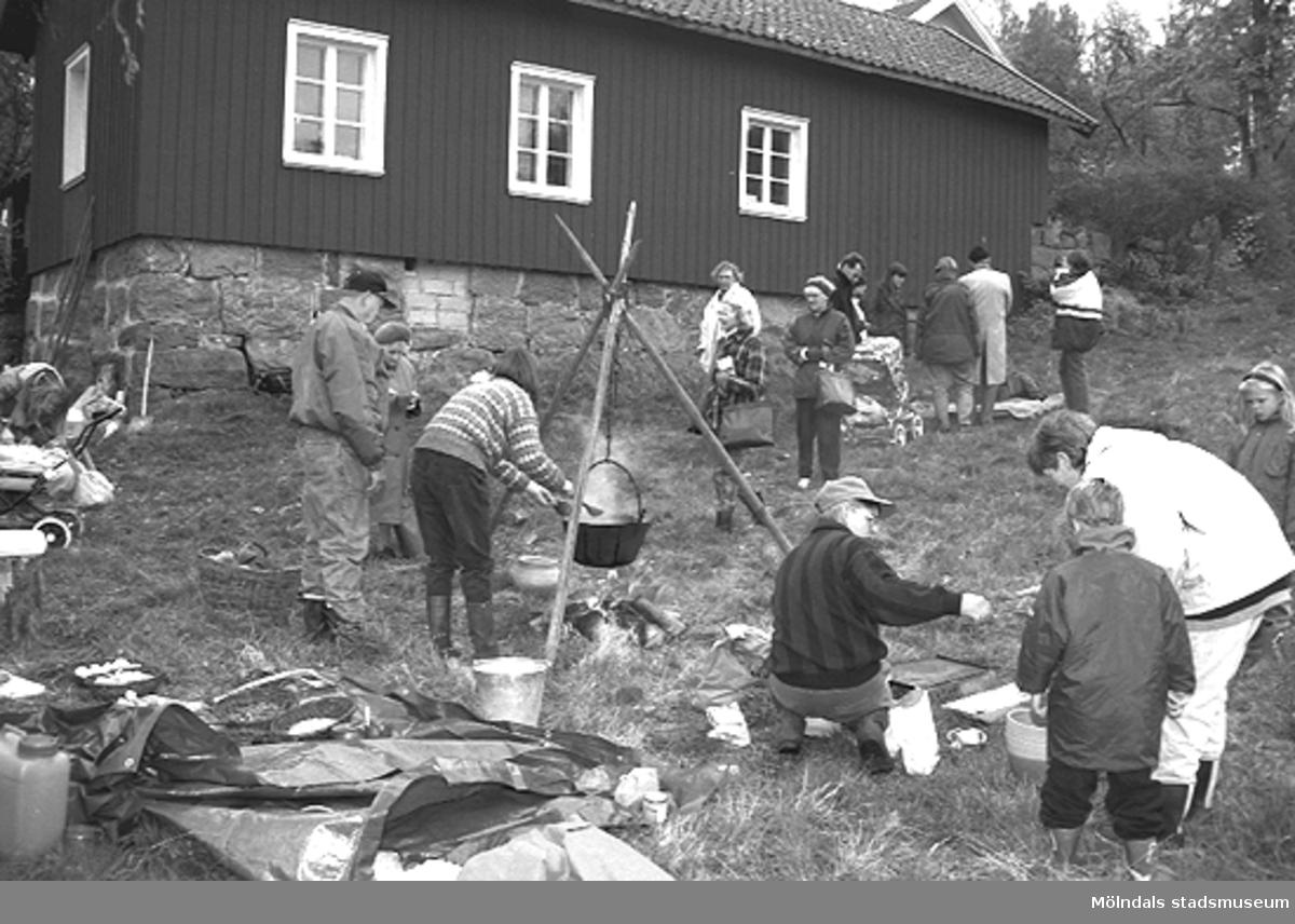 Familjesöndag vid Börjesgården, 1994-05-15. Besökare ser på när Museichef Mari-Louise Olsson kokar soppa över öppen eld. Sittandes på huk är museitekniker Alf Garthman.