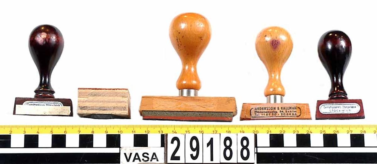 """Fem trästämplar från Vasanämnden. Stämpel 1: Brunt träskaft """"Bestyrkes i tjänsten"""" Stämpel 2: Fyrkantig """"Wasanämnden"""" med bild av kärven. Stämpel 3: Stor med träfärgat skaft """"Wasanämnden Vidimeras: Granskad utan anmärkning Utbet. tillstyrkes Konto"""" Stämpel 4: Träfärgat skaft """"Tjänste Statens Sjöhistoriska Museum Wasanämnden Stockholm 100"""" Stämpel 5: Brunt träskaft """"Wasanämnden"""""""