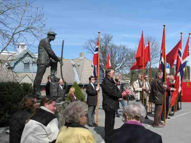 1.mai på Eydehavn. Skulpturen Industriarbeideren og flaggborgen.  Appell ved Jan Arild Andersen - ved mikorfonen.