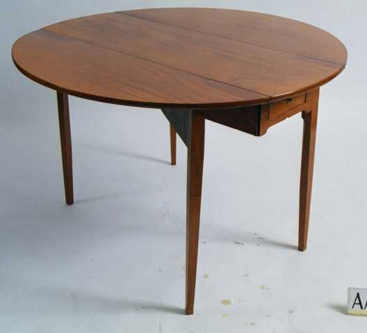 Klaffebord, av mahogny,  polert.  Bredt klaffebord med rundede klaffer.  En skuff med messingknott i hver ende. Rette ben.