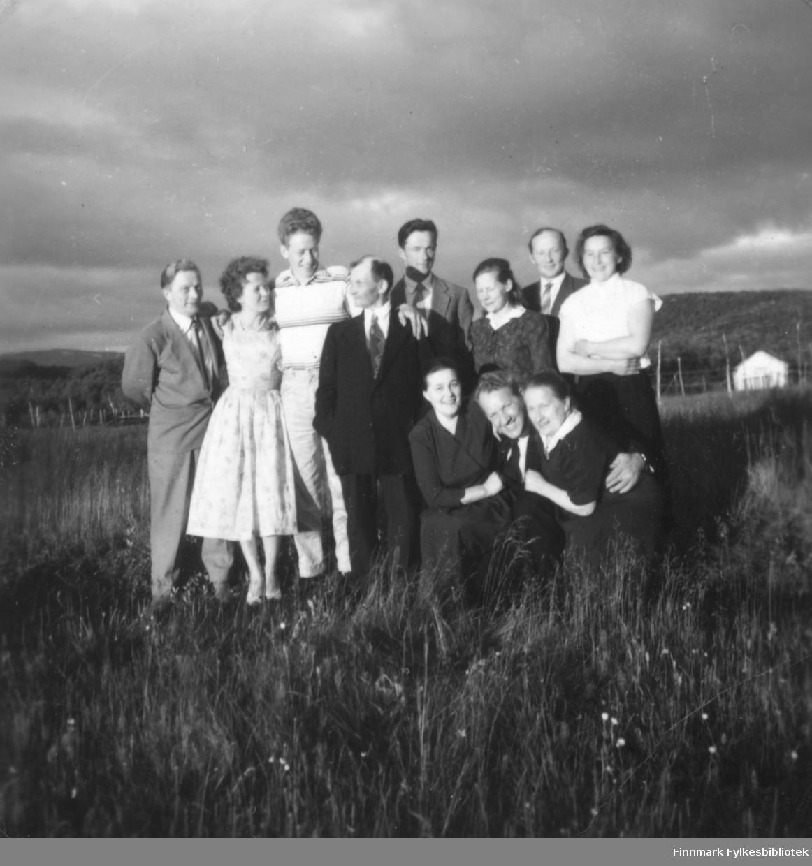 En gruppe pentkledte mennesker fotografert i terrenget i Ildskog i Porsanger. De er fra venstre: John Johansen, Gunhild Guttorm, Gunhilds mann, Nils Guttorm, Helmer Jolma, Thekla Jolma, Johannes Nymo, Anne Marie Nymo. Sittende ses Ragna Liland, Kristian Liland og Nanna Guttorm.