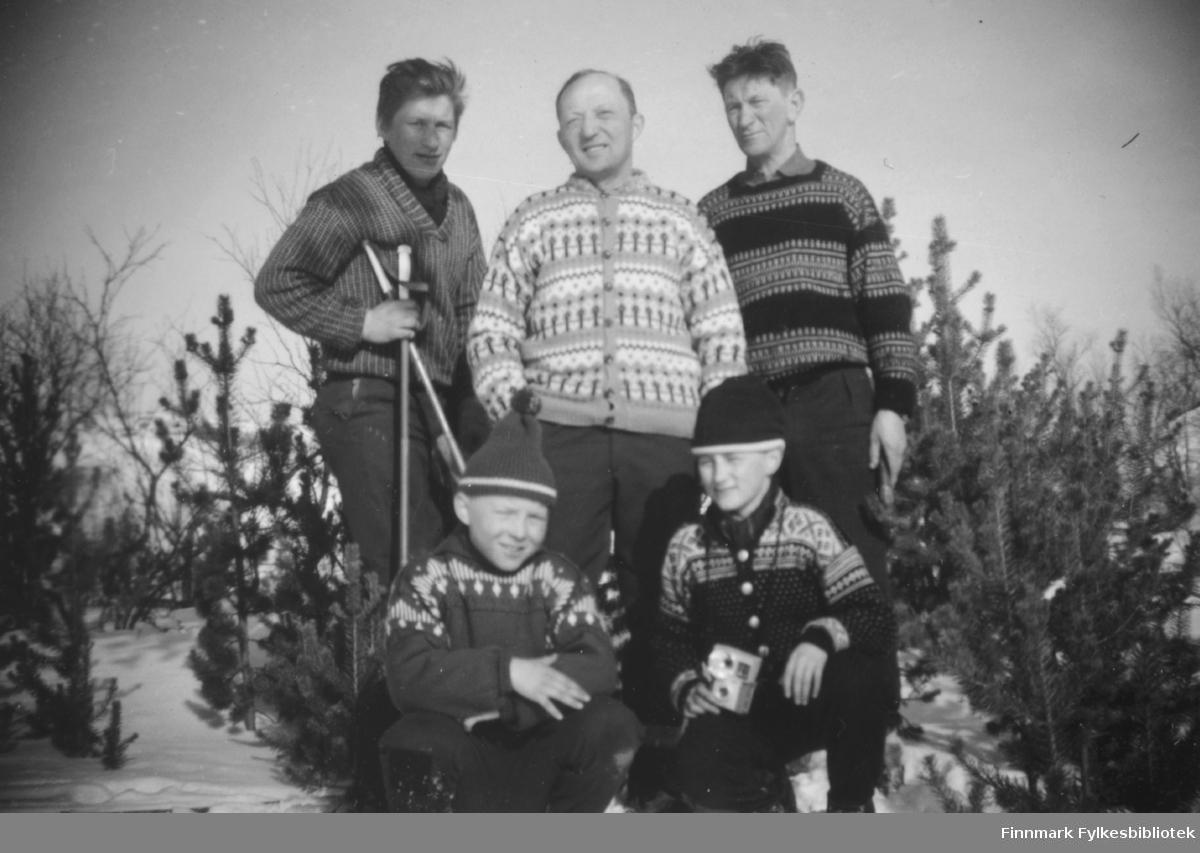 Tre menn og to gutter fotografert utenfor skogvokterhytta i Rochi i Porsanger. Bak fra venstre står Idar Hansen, Johannes Nymo og skogvokter Erling Hansen. Foran fra venstre sitter Kjell Nymo og Bjørn Malin.