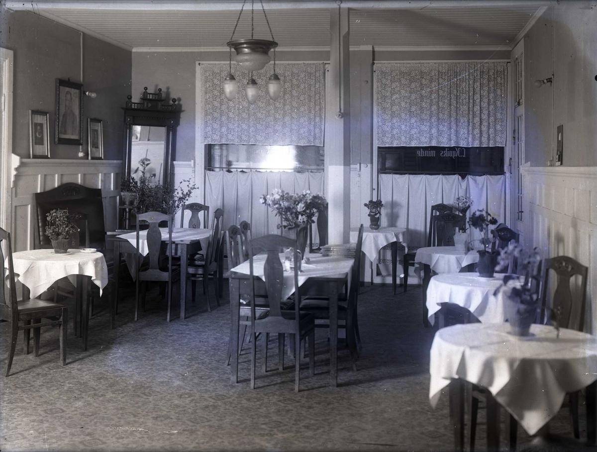 Interiør - Kafè-interiør med småbord. Blomster på alle bordene. På vinduet står: L. Kyviks Minde.