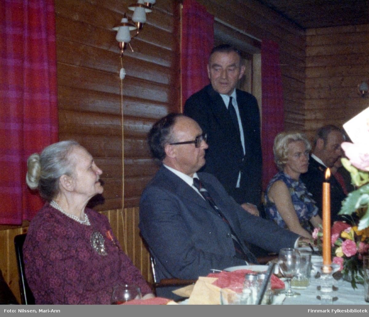 Marie Sivertsen ble tildelt Kongens fortjenestemedalje i gull under en høytidelig tilstelning på Neiden fjellstue, 3. mai 1977. På dette bildet taler ordfører Arnt Isaksen. Fylkesmann Anders Aune til venstre for ordfører Arnt Isaksen.