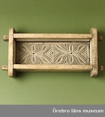 Ostform. Trä. Avlång form. Botten dekorerad med mönster i karvsnitt, bestående av blommor och ornament. Mönstret symmetriskt. På ena långsidan står årtalet 1834 insnidat. Uddsnitt förekommer också.  Från Solberga gård, Hallsberg.  Gåva av Greve Eugene Lewenhaupt Säbylund.
