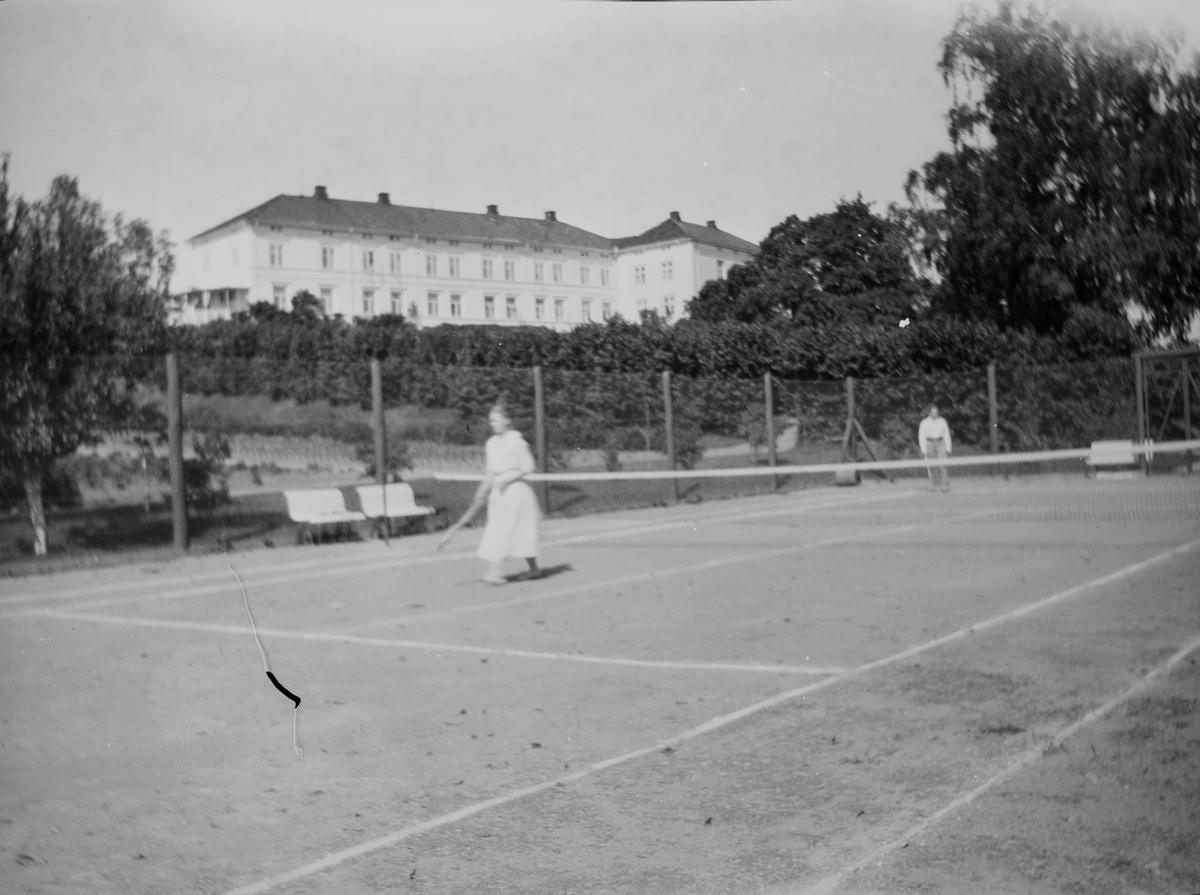 Tennisbane på Linderud gård om sommeren. En mann og en kvinne spiller tennis. I bakgrunnen; hage og hovedbygning.