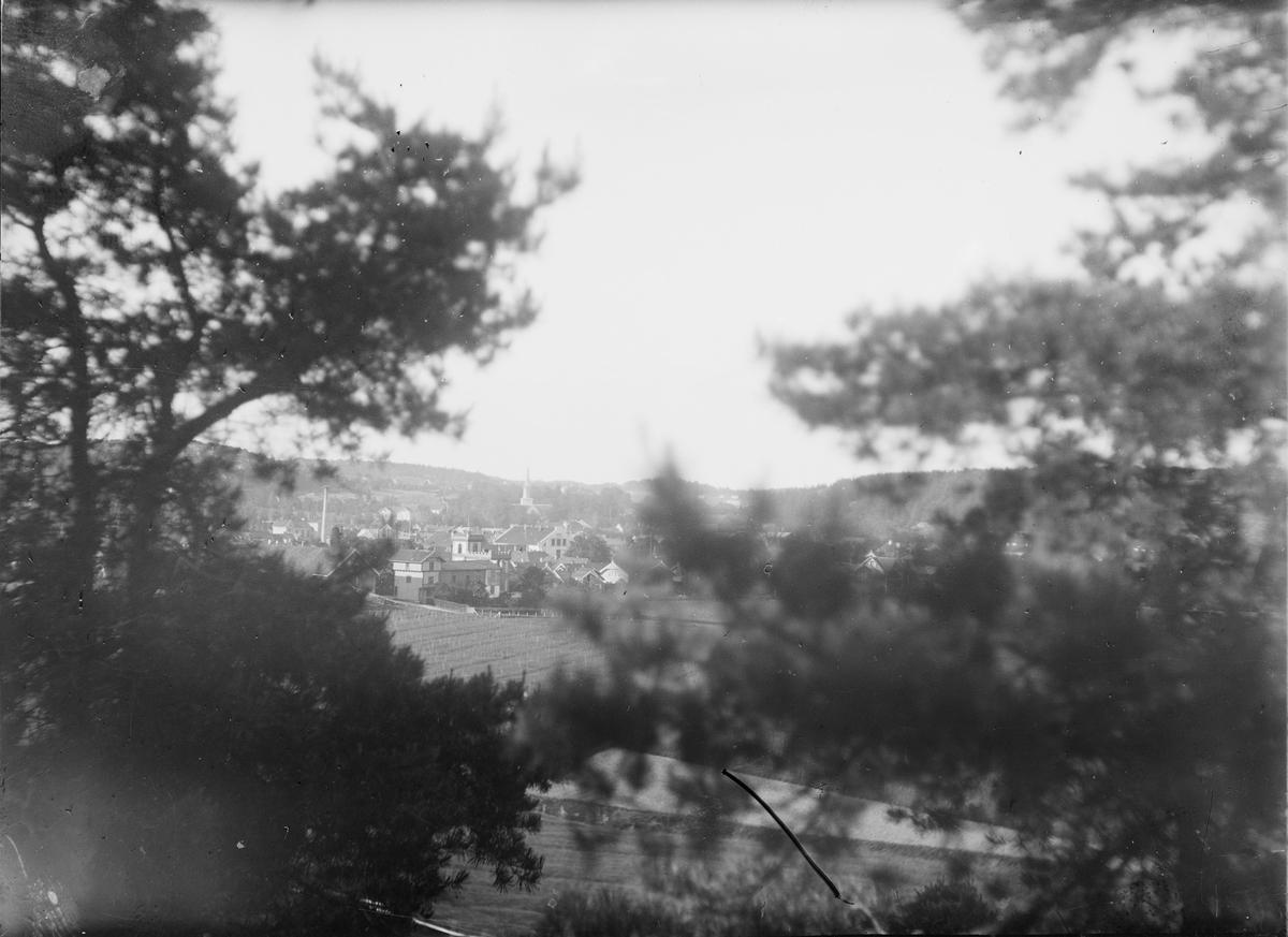 Landsby med omkringliggende jordbrukslandskap. Bildet er tatt gjennom en åpning mellom trær.