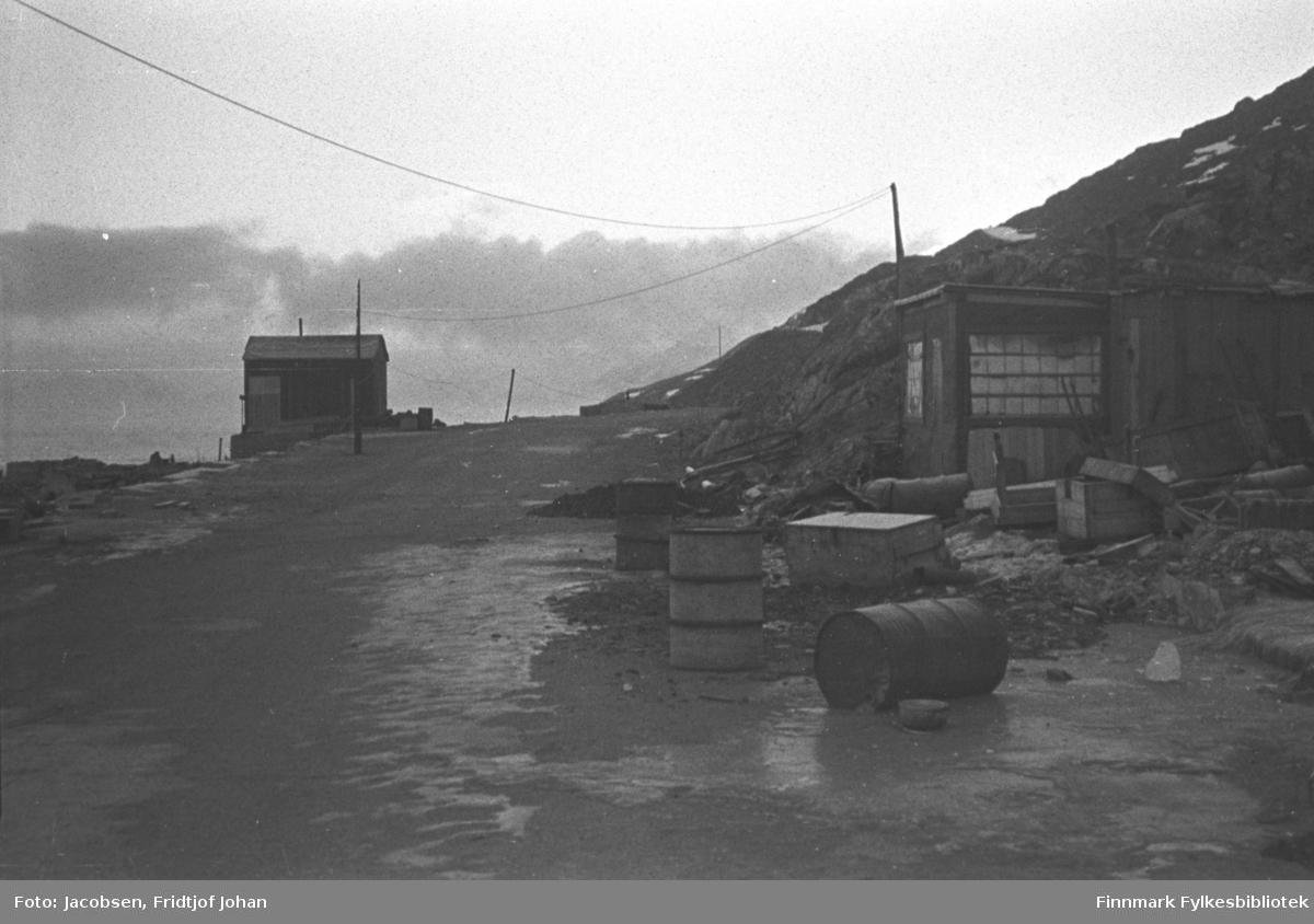 Et par brakker er satt opp i Hammerfest. En brakke står til venstre på bildet med langveggen mot kamera. En liten, tynn skorstein ses på taket og noen gjerdestolper står nedenfor den. En grusvei går bortover mot brakka. På høyresiden av veien står en brakke til. Denne kan være et verksted/lager. På plassen foran den ligger flere trekasser i varierende størrelse. Tre tønner står og ligger i veikanten. Et fjell som skrår endel står til høyre på bildet. Fjellet har noen små snøflekker og en el-stolpe står i skråningen. En ledning går fra den til stolpen ved brakka og fra den og mot venstre på bildet. Tunge, mørke skyer ses i horisonten.