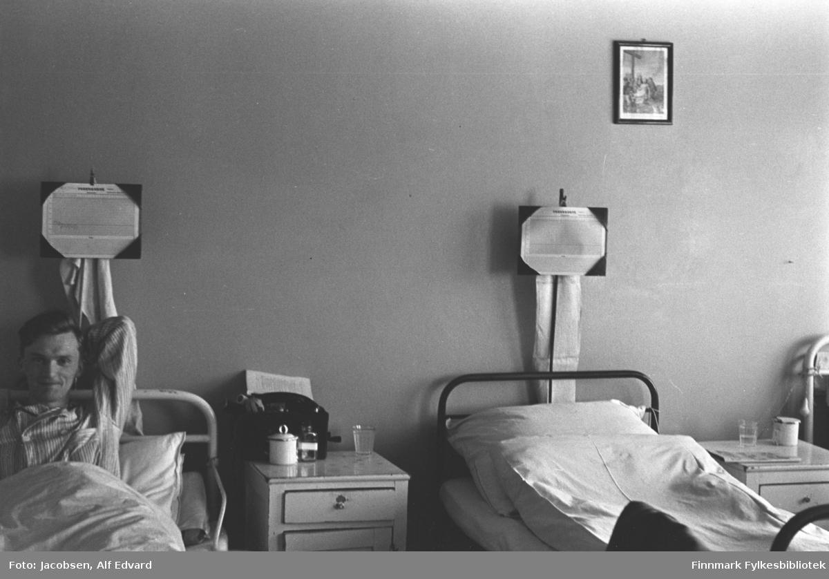 Fridtjof Jacobsen på St.Vincents Hospital med ene armen bak hodet. Han har en stripet pysjamas på seg. Han ligger i en seng med hvit metallramme. Det er hvite/lyse sengeklær og bak hodegjerdet på sengene står et stativ med et skriv, kanskje info til pasientene. Et lyst nattbord med to skuffer står ved siden av sengene. Oppå det som er nærmest Jacobsen står to glass, en liten skål med lokk og en toalettmappe. Den andre