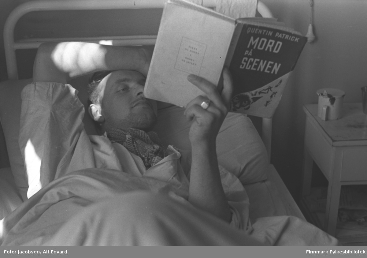 En mann ligger i senga si på St. Vincents Hospital. Han ligger på rygg og har høyre armen over hodet. I venstre hånd holder han en bok, Mord på scenen. En bred ring ses på venstre ringfinger. Senga han ligger i har hvitlakkert metallramme. Sengeklærne er også hvit/lys. I halsen har han noe stripet tøy, muligens et tørkle eller skjerf. Den kortermede skjorta han har på er hvit/lys. Ved siden av senga står et hvitt nattbord med en skuff øverst og en hylle under. Oppå står et krus og et glass. Veggen er lys og ensfarget og enden av en snor ses oppe til høyre.