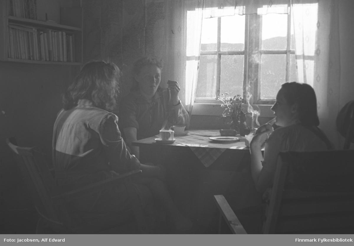 Aase Randi Jacobsen, mor til Arne Jacobsen, har besøk av to venninner i Rypefjord. Aase lengst til høyre på bildet har en ganske lys, kortermet overdel på seg. Damen i midten har også en kortermet bluse på seg, men den er litt mørkere enn Aases. Et armbånds ses på venstre håndledd. Til venstre sitter en dame med ryggen mot kamera. Hun har også en ganske lys bluse på seg. De sitter i forholdsvis enkle lenestoler. Bordet de sitter ved er av tre og har en mønstret duk oppå. Tre kopper med varm drikke står foran dem på tefat og dampen stiger opp fra alle koppene. En liten blomst står også på bordet nærmest vinduet. En liten skål eller muligens et askebeger stor foran blomsten. Et vindu med sprosser og hvit stolp og karmer står på veggen lengst fra kamera. Noe sol skinner gjennom glasset. Lyse og ganske tynne gardiner med kappe henger rundt og over vinduet. Helt til venstre på bildet står en bokhylle med en del bøker oppstilt.