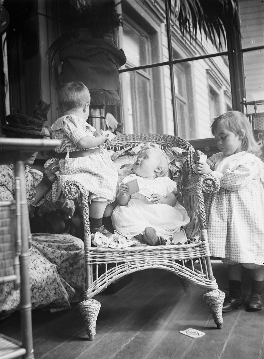 To barn sitter i en kurvstol på en veranda imens en kvinne, sittende på huk, passer på. Et større barn står ved siden av stolen og konsentrer seg om noe hun holder i hånden. På bakken ligger et spillkort. I bakgrunnen sees vinduer inn til huset og blomstrende hortensiaer.