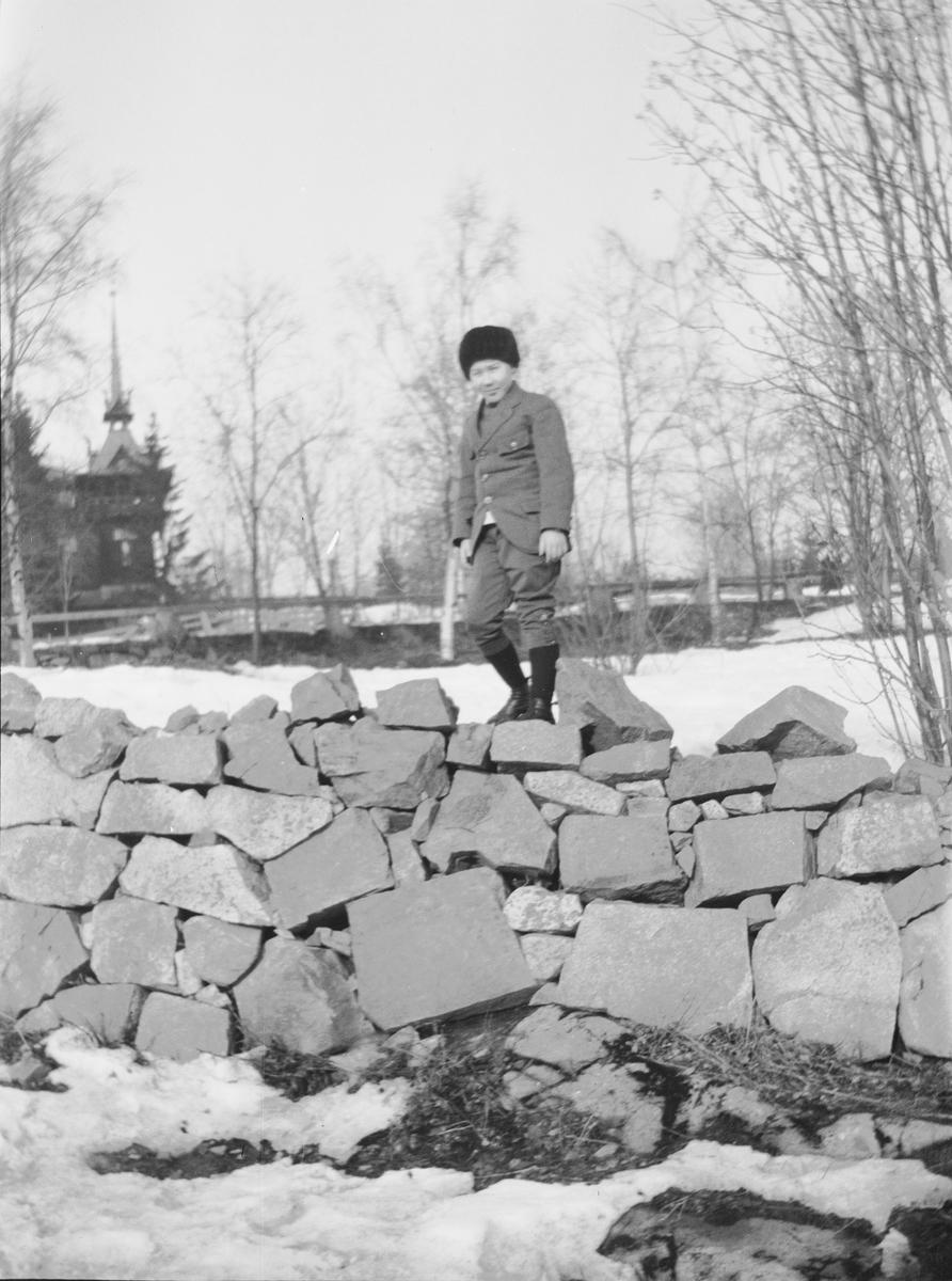 Bildet er kanskje tatt ved Holmenkollen Turisthotel og det er Iacob Ihlen Mathiesen som står på toppen av en tørrmur eller steinmur.