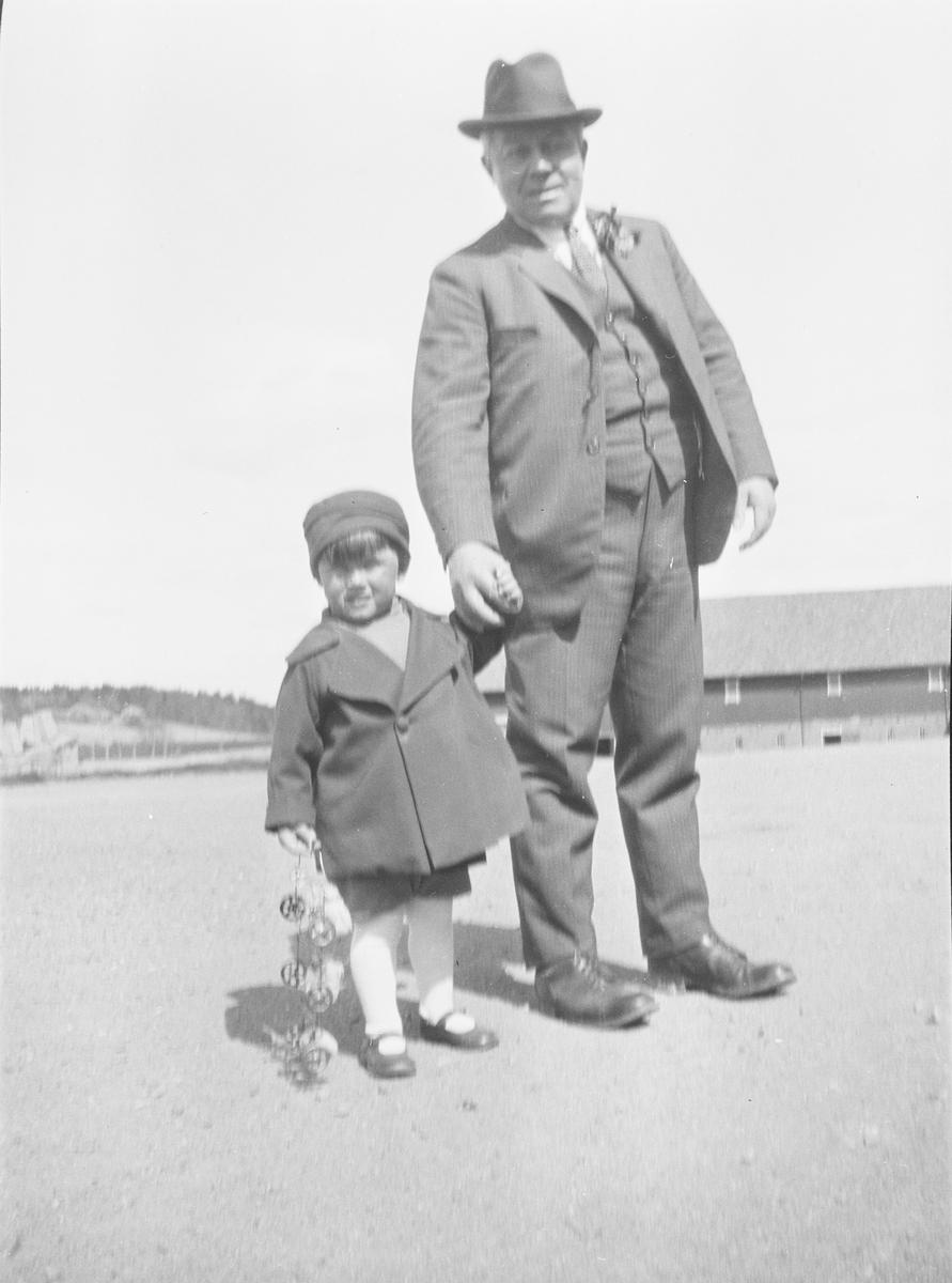 Christian Pierre Mathiesen holder et lite barn i hånden. De står sammen på gårdsplassen til Linderud gård en solskinnsdag. Barnet, kanskje et barnebarn, holder noe i hånden som sannsynligvis er en leke.