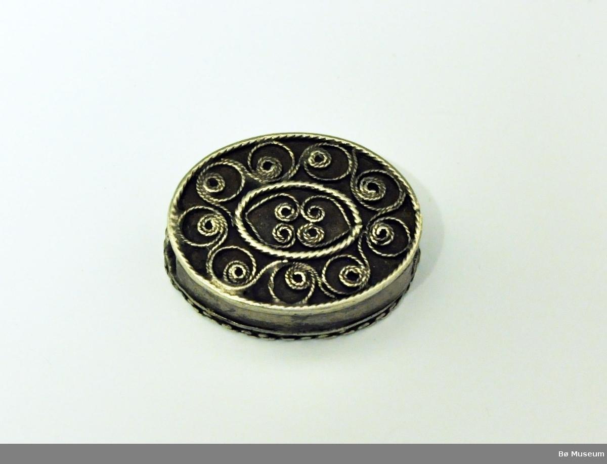 Låseanordning? eller anheng? for kjede, antagelig klokkekjede. Oval form - hull i hver side (tvers gjennom). Dekor på oversiden; filigransarbeid (se bildet).