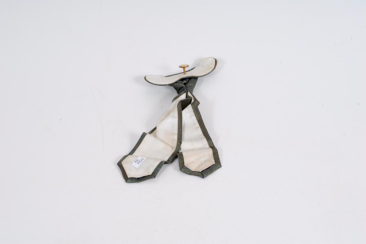 Form: slipsknute med to ganske korte ender nedover og med et lite stivt stykke til å feste den i snippen med og en utstående knapp bak det stive stykket