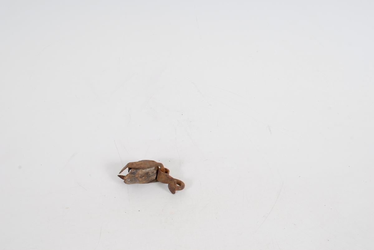 """Form: Svungen krok med flate, rette mothaker, ..*23 ..hengslet til beslag somomslutter enden av trestav eller lign. Beslaget festet med to gjennomgående klinknagler. R.K.:""""Jeg kan tenke meg det er nederste enden av en drastaur, slik som de brukte når de dro skikjelken"""". Gave. Kommunen  kjøpte gården og R.K. fikk plukke ut ting til museet. I ei kasse fra smia."""
