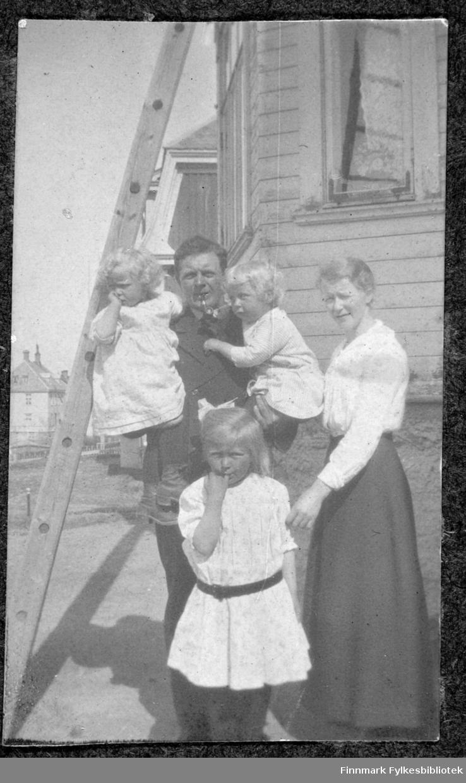 Familie under stige ved hus.