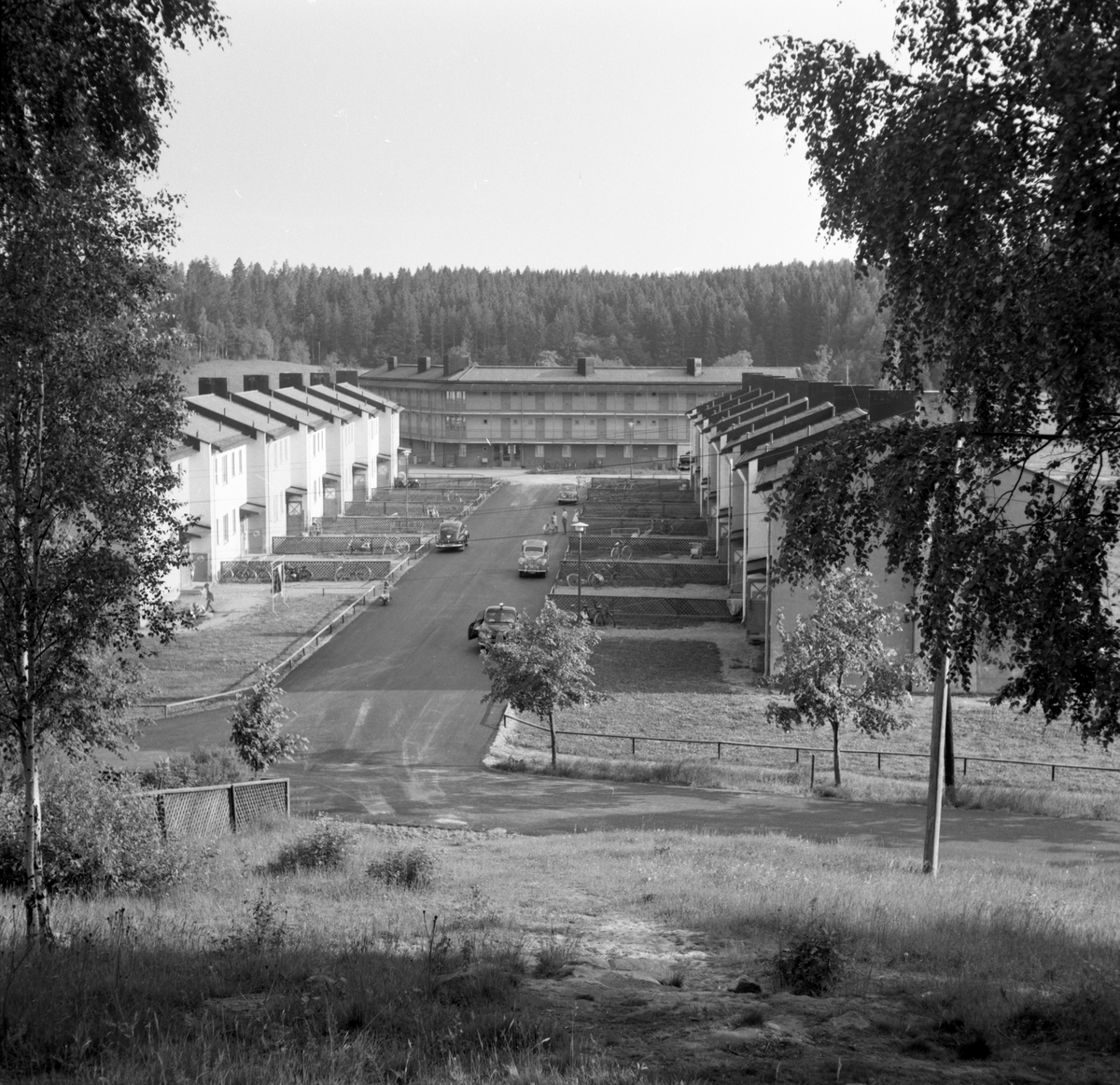 """Någonstans i Värmland - från slutet av 1950-talet.  Kommentar från en användare: Älvenäs, gatan rakt fram är Spinnaregatan, och längst ner ligger ungkarlshotellet. Alla husen är rivna men gatan finns kvar! Jag bodde i det vänstra huset 1966. Bakom granskogen går i dag E18 fram. Ungkarlshotellet kallades också i folkmun för """"Sing Sing""""p.g.a sin utformning."""