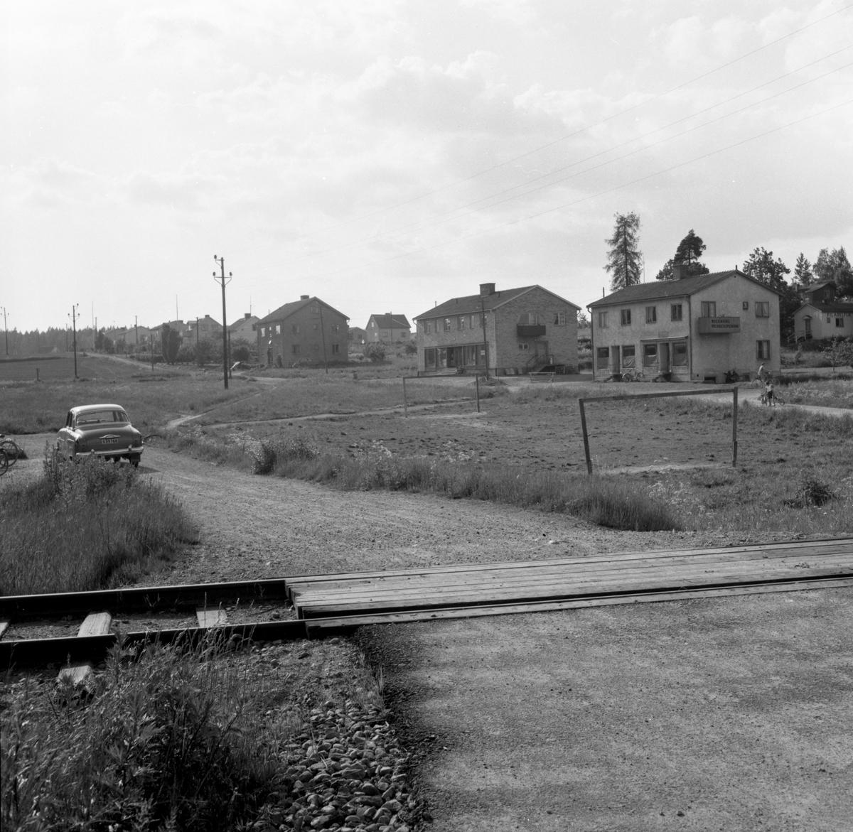 Någonstans i Värmland - från slutet av 1950-talet. Älvenäs, gatan till höger är Åkergatan. Järnvägen som syns går till vänster ner till Rayonfabriken och till höger in till Vålberg. I första byggnaden fanns Wickmans Herrekipering