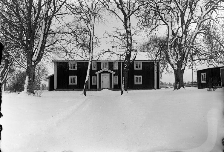Foto av en mangårdsbyggnad i snö.
