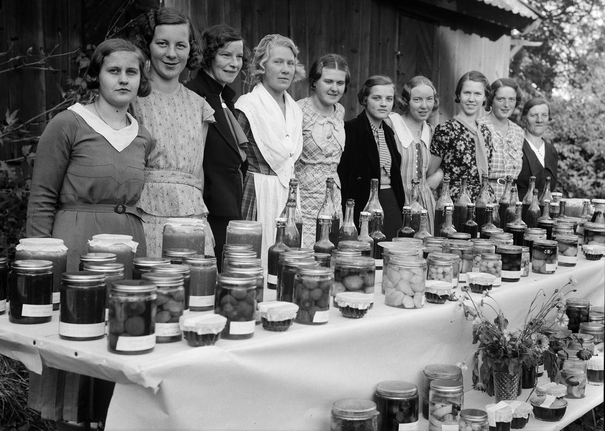 """Hemkonsulent Rut Ingeborg Jonsson (nr 4 från vänster, Högstedt som gift) omgiven av kursdeltagare i den veckolånga konserveringskurs som gick av stapeln i prästgården i Björklinge hösten 1934. Björklinge husmodersförening anordnade kursen medan Hushållningssällskapet bekostade den. Hemkonsulent Jonsson hade hållit liknande kurser i Hjälsta, Nysätra, Alunda, Hacksta och Bälinge. Hon tyckte att """"vad man framför allt får lägga an på är att lära eleverna lättare och bättre arbetsmetoder i konserveringsarbetet."""""""