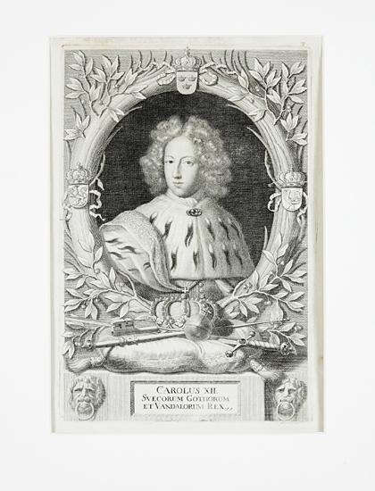 """Kopparstick (reproduktion ?).  Porträtt föreställande Karl XII (1682-1718), som ung med allongeperuk m.m. inom lagerkrans. Latinsk text: """"Carolus XII, Svecorum, Gothorum et Vandalorum Rex""""."""