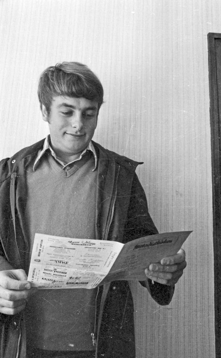 Portrett. Ung mann som studerer informasjonsskriv fra Metodistkirken.