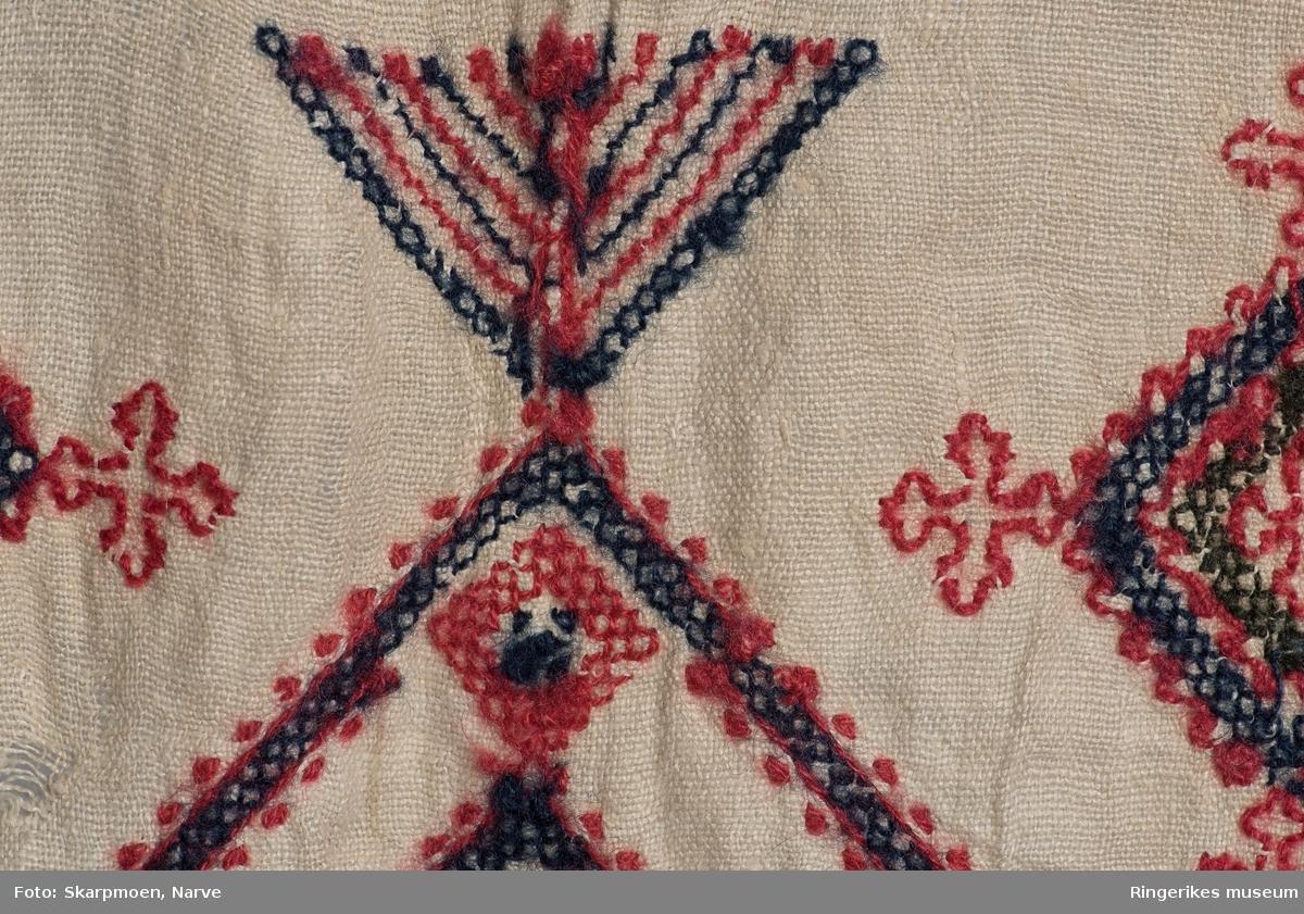 Kvadrater stilt på høykant, små kors og 8 armete staker? Motivene er stilt i rader over hele duken. Gjenombrutt bord med kvadrater i en kortende