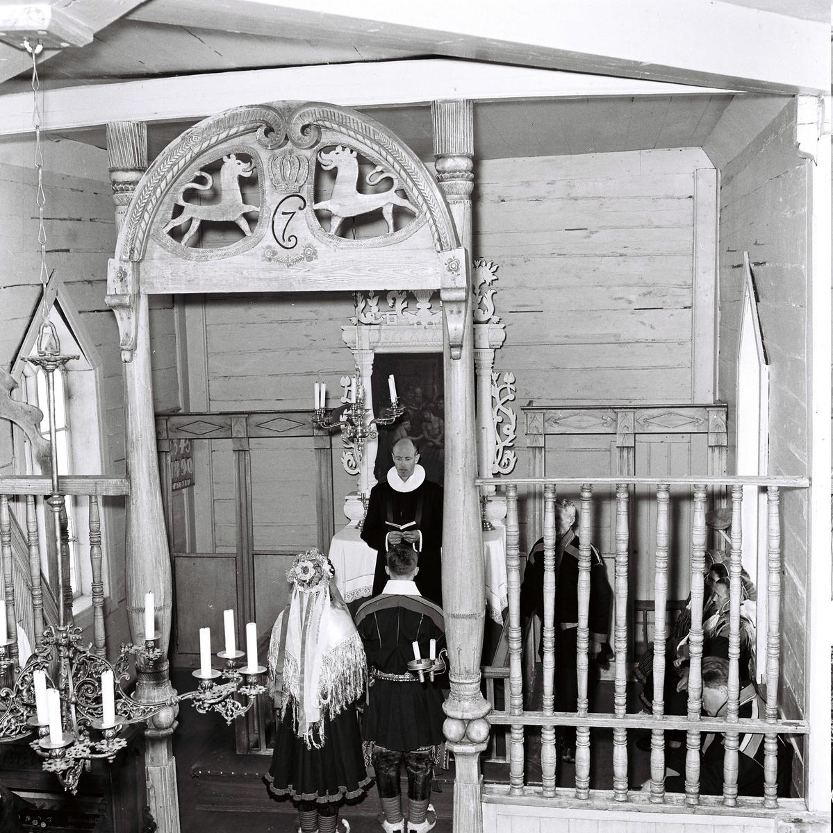 Karasjok kirke, altertavlen og prekestolen. Korskirke i tre fra 1807..Presten vier et samisk brudepar. De har tradisjonelle samiske festdrakter.
