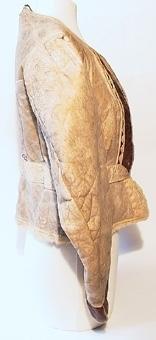 Kvinnotröja av vitt fårskinn med svängd skärning samt avskuren i midjan. Ryggen är skuren i tre stycken och har skört mitt bak. Halsringningen är rund och tröjan knäppes framtill med hyskor och hakar av mässing. Smala skinnremsor täcker sömmarna och en bredare remsa täcker midjesömmen. Brunt nappaskinn är påsytt på jackans framstycken och vid underkanten av ärmarna.