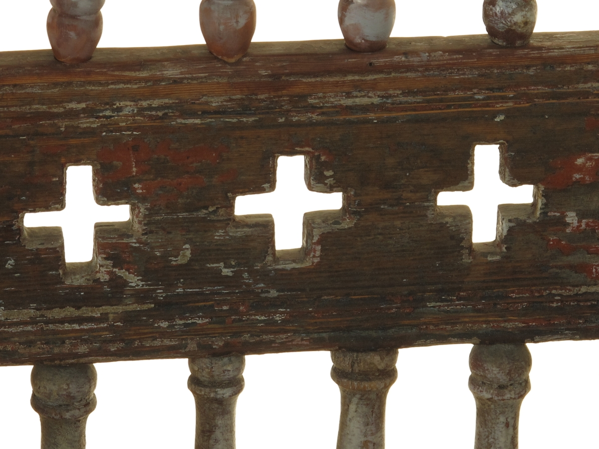 Senmiddelaldersk type, av dreiede pinner. Muligens opprinnelig kirkestol, da der er rader med kors i ryggen. Armlenene har på undersiden festet 6 små  balustre, som nedentil er festet i nok en dreiet tverrligger. Der har likeledes vært balustre (3 stk) under sargen i fronten ned til den øvre tverrstreber. Ryggen består av avvekslende dreiede balustre i tett  rad og horisontale bretter med utskårne gjennombrutte kors. Buet toppstykke. Endene av bakstavene har dreide knotter.