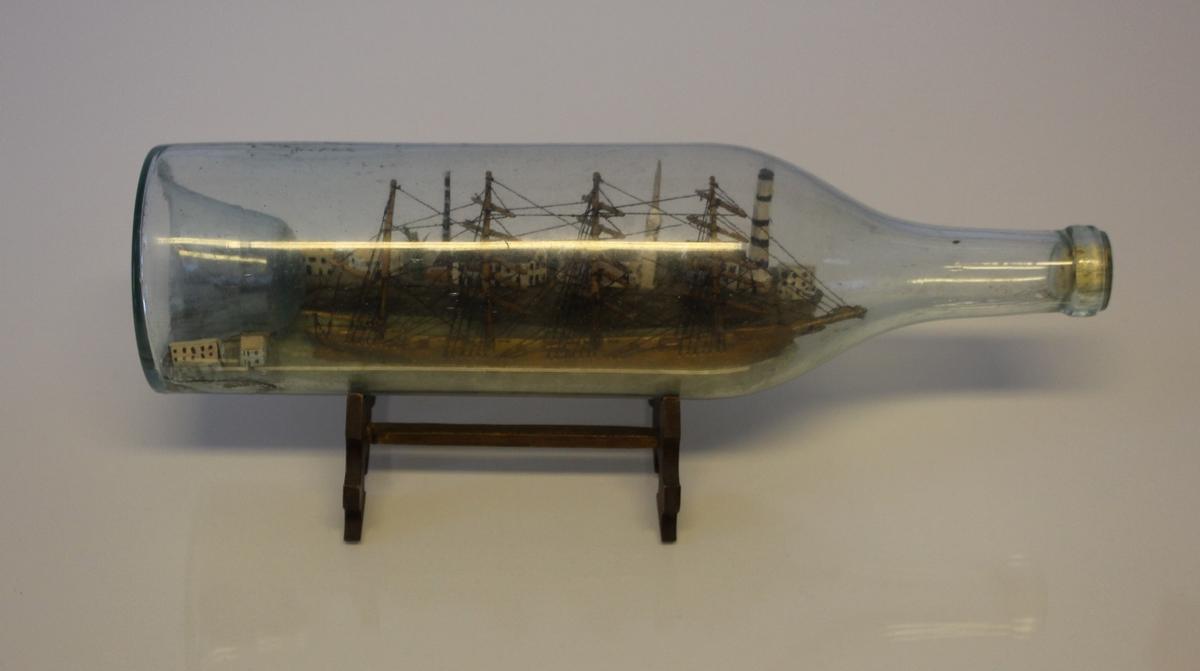 Bark med en del seil oppe i firkantet flaske. Skipet fører unionsflagg på mesantoppen.
