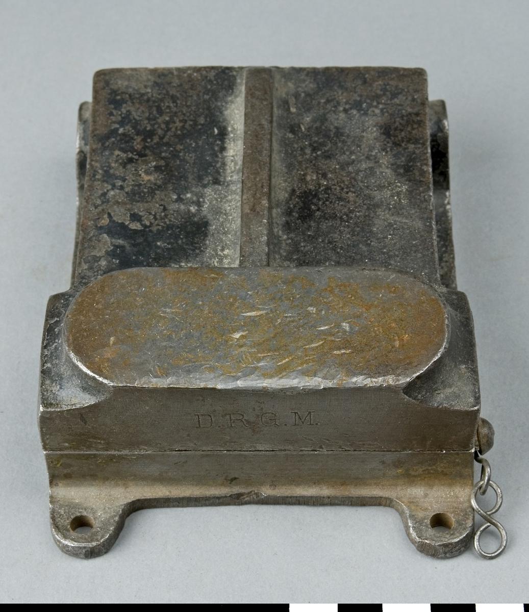 Klammerpress i gjutet utförande för fastpressning av klammer i transmissionsrem vid skarvning. Klammerpressen består av två plattor där den främre delen utgörs av en pressback, där den undre har en mässingsback för låsning av klammersatsen vid fastpressning. I den bakre delen av bottenplattan sitter den övre pressplattan ledad. Vid fastpressning av klammer lägges änden på remmen och klammersatsen mellan pressbackarna. Genom slag på den övre pressbackens slagyta pressas klammer in i remmen. Bottenplattan har tre hål för fastskruvning i bänk. Klammerpressen är stämplad D.R.G.M.  Funktion: Skarvning av drivremmar