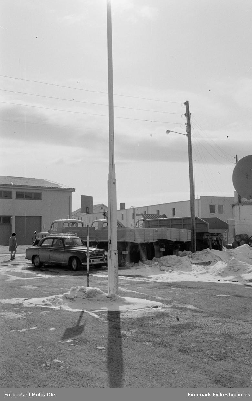 Fotoserie fra Vadsø, April 1968 fotografert av Vadsøfotografen Ole Zahl-Mölö. Vadsø by. En flaggstang ruver i front i bildet. Parkerte biler (nærmest er Peugeot 403) og lastebiler i bakgrunnen.
