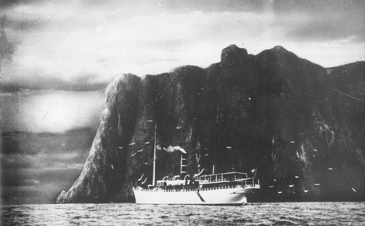 """""""Midnattssol Nordkap. Aug. 1937"""" står det på glassplaten. DS «Midnatsol» (kallesignal MGBT / LELR) var et hurtigruteskip som ble overlevert Det Bergenske Dampskibsselskab (BDS) i juni 1910. Skipet var byggnummer 158 ved Bergens Mekaniske Værksted, og kontraktsummen var 504 032 kroner. I juni 1910 ble DS «Midnatsol» satt i hurtigrutetrafikk. Hun gikk i fast rotasjon fram til 1950, bare avbrutt av verkstedopphold. Skipet ble hugget opp i Belgia i 1954.I 1930 ble innredningen bygget om og modernisert. I 1936 ble det innført daglige avganger i hurtigruten, og DS «Midnatsol» var et av de 14 skipene som gikk i fast rotasjon. DS «Midnatsol» hadde en tonnasje på 978 bruttoregistertonn, 505 nettoregistertonn, og lasteevnen var på 510 dødvekttonn. Skipet hadde lasterom foran og aktenfor kjelerommet, og lasting og lossing foregikk med skipskraner forut og midtskips. Hovedmaskinen var en kullfyrt trippel ekspansjon dampmaskin bygd ved Bergens mekaniske verksted. Oppgitt ytelse var 1 508 ihk (indikerte hestekrefter) og 233 nhk (nominelle hestekrefter), og på prøveturen oppnådde skipet 13,44 knop. Ved levering hadde hun 132 køyeplasser fordelt på 53 på 1. plass (1. klasse), 34 på 2. plass, og 45 på 3. plass. Plasseringen av passasjerklassene var tradisjonell, med 1. plass akter, 2. plass midtskips, og 3. plass forut. 1. plass spisesalong hadde store vinduer, og lå midtskips på stormdekket. På dekket over (promenadedekk) lå 1. plass røkesalong, og over denne lå den åpne kommandobroen med bestikklugar og kapteinlugar like bak."""
