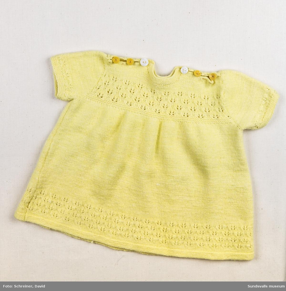 En stickad gul klänning med högt placerat liv. Mönstersickning i ärmslut, halsringning, livet och i klänningens nederkant. Knäpps med tre stycken gula plastknappar över de båda axlarna.
