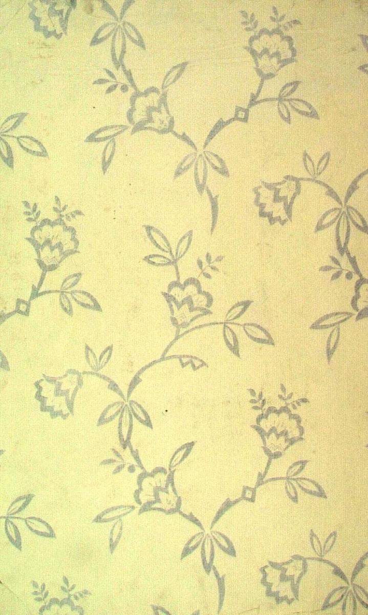 En strängt stiliserat slingrande blommönster i ljusgrått och cremegult.
