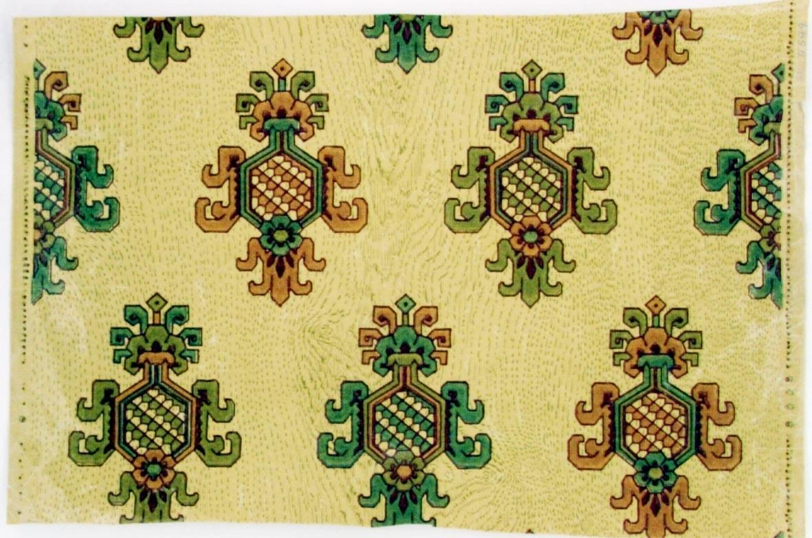 Träimiterande mönster dekorerat med ett stiliserat liljan ornament i diagonalupprepning. Tryck i beigrått samt i två gröna och två gammalrosa nyanser på ofärgat papper.