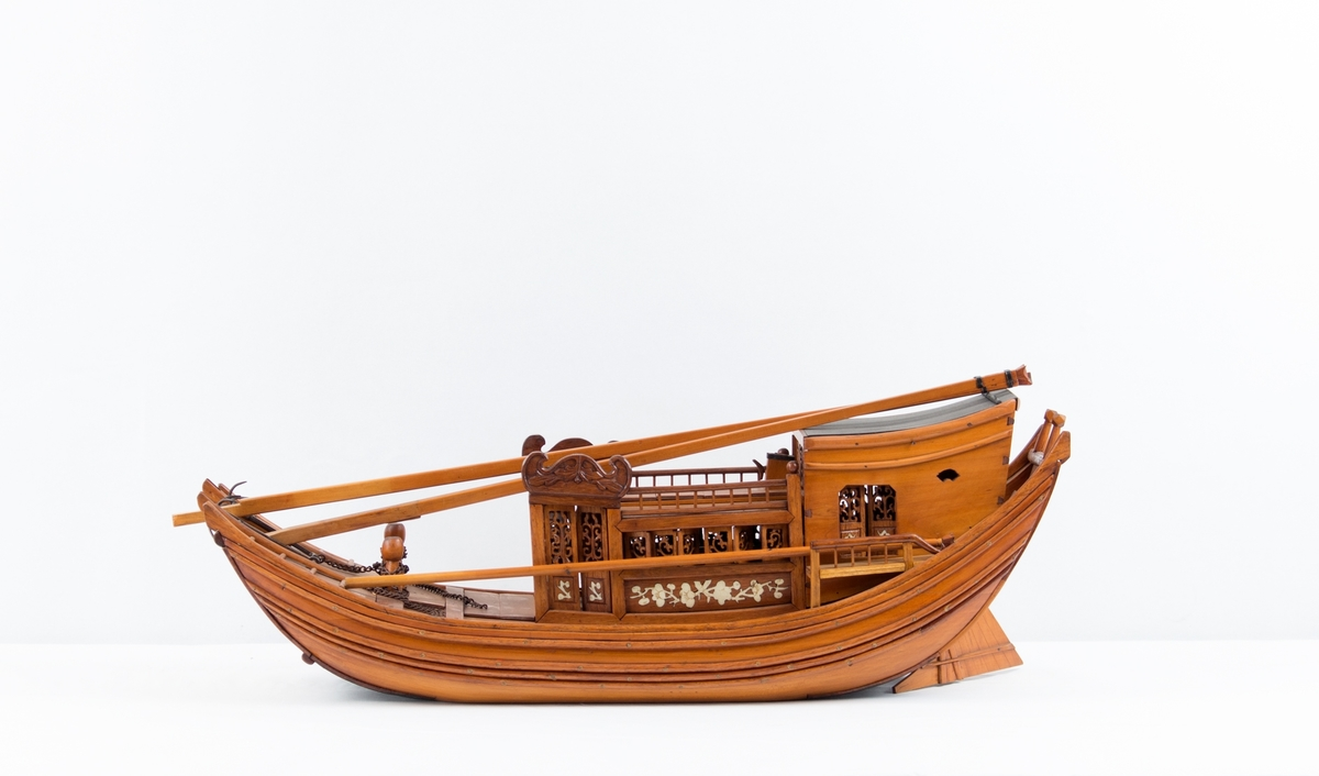 Modell av kinesisk djuke, rikt dekorert med utskjæringer og intarsia med bein. Mastene ligger løst på dekk.